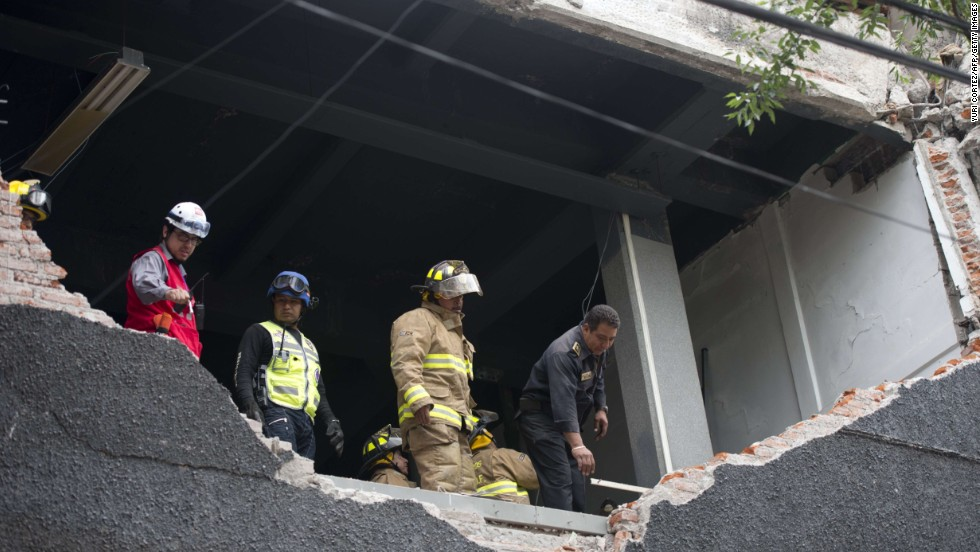 Firefighters in Mexico City examine a damaged wall.