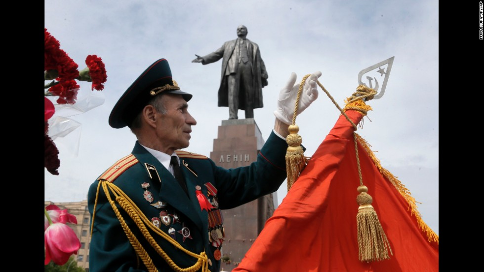 A veteran adjusts a Soviet Army flag in front of a monument of Vladimir Lenin during a Victory Day celebration in Kharkiv, Ukraine.