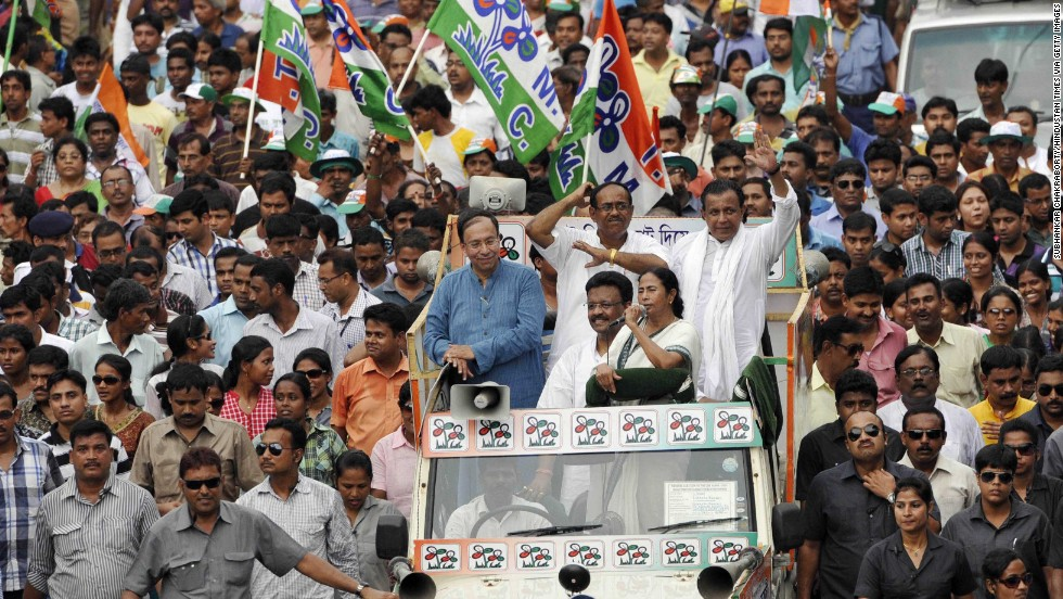 Trinamool Congress Chairwoman Mamata Banerjee, with microphone, campaigns for Jadavpur TMC candidate Sugata Bose, left, and South Kolkata candidate Subrata Bakshi, center, with Mithun Chakraborty on May 10 in Kolkata.