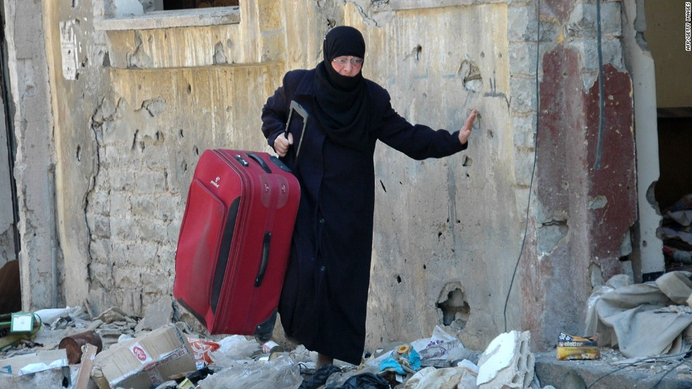 A Syrian woman carries a suitcase along a street in the Juret al-Shayah district of Homs on May 10.
