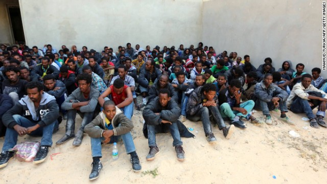 Some of the 340 illegal migrants who were rescued by the Libyan navy off the coast of the western town of Sabratha when their boat began to take on water, sit at a shelter on May 12, 2014 in the coastal town of Zawiya, west of Tripoli. The rescue came on the same day Italy's navy said at least 14 migrants had died when their boat sank between Libya and Italy, the latest in a string of shipwreck tragedies to hit the Mediterranean. Libya has long been a springboard for Africans seeking a better life in Europe, and the number of illegal departures from its shores is rising. AFP PHOTO / MAHMUD TURKIA        (Photo credit should read MAHMUD TURKIA/AFP/Getty Images)