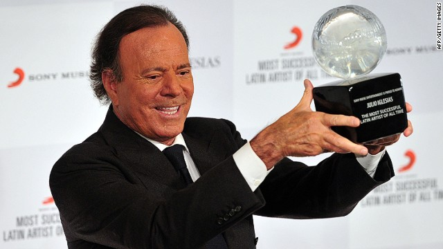 Spanish singer Julio Iglesias holds an award after being named the most successful Latin artist of all time at a press conference in London on May 12, 2014. AFP PHOTO / CARL COURTCARL COURT/AFP/Getty Images