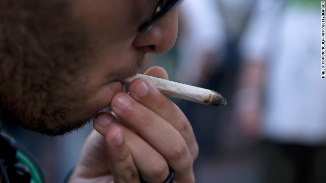 A man smokes a joint during a march for the legalization of marijuana towards the Legislative Palace in Montevideo, on December 10, 2013, as the Senate discuss a law on the legalization of marijuana's cultivation and consumption.