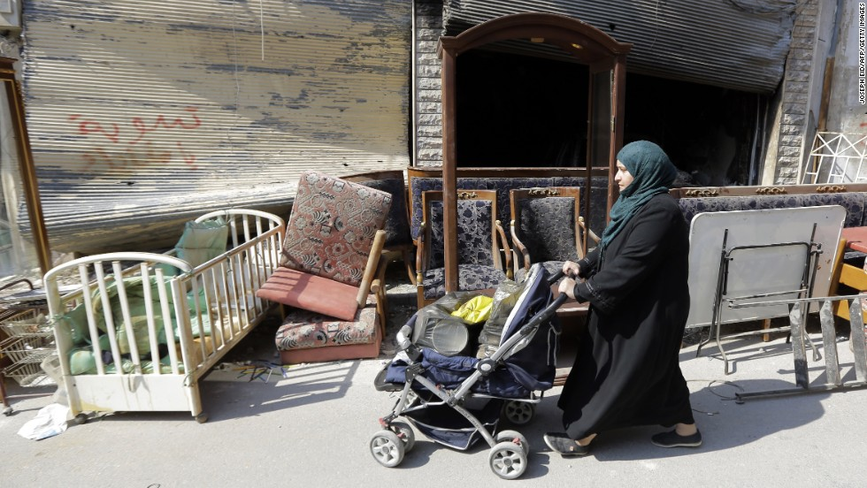 A Syrian woman pushes a baby stroller packed with belongings past furniture left on the side of the street in the Old City on May 12.