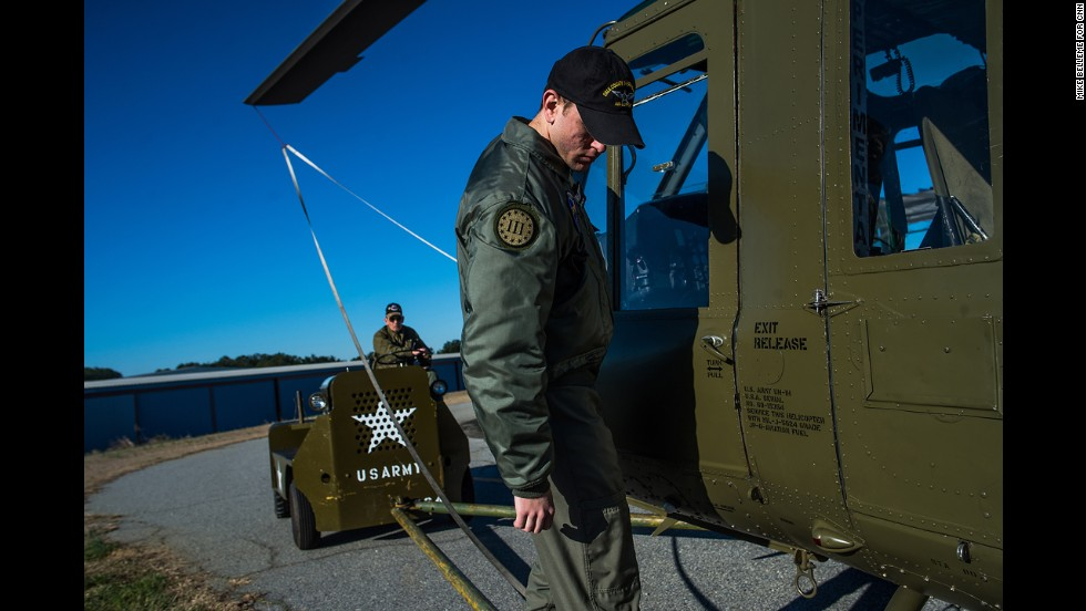 Foundation volunteer Tyler Phillips hops aboard a restored Huey helicopter as it is towed from the hangar to the tarmac in preparation for flight in Hampton.