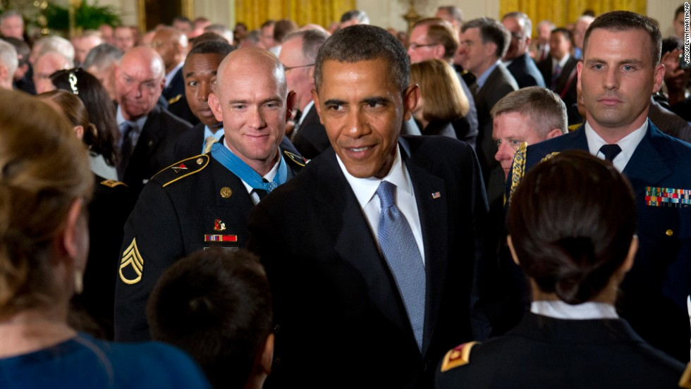 "Army Staff Sgt. Ty M. Carter, left, watches as Obama greets family members of fallen service members after Carter was awarded the Medal of Honor in August 2013. Carter was cited for his actions during the October 3, 2009, defense of Command Outpost Keating in Afghanistan, including ""running through a hail of enemy rocket propelled grenade and machine gun fire to rescue a critically wounded comrade."""