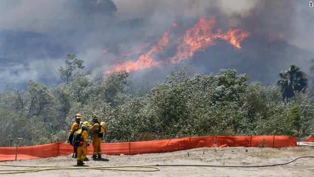 Frefighters battle a wild fire Tuesday, May 13, 2014, in San Diego. Wildfires destroyed a home and forced the evacuation of several others Tuesday in California as a high-pressure system brought unseasonable heat and gusty winds to a parched state that should be in the middle of its rainy season. (AP Photo)