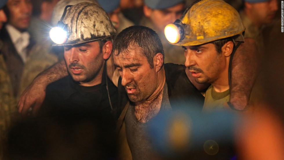 Rescuers help carry away a miner on May 14.