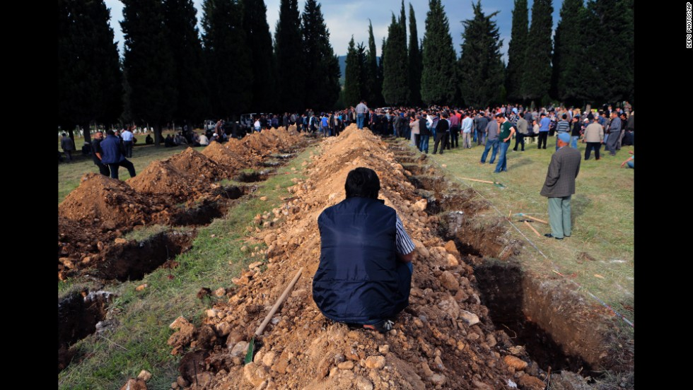 People gather near rows of open graves for victims in Soma on May 14.