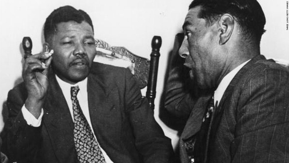 "<a href=""http://www.cnn.com/SPECIALS/africa/nelson-mandela/index.html"">South African resistance leader Nelson Mandela</a>, left, talks to Cape Town teacher C Andrews in 1964. On June 12, 1964, Mandela was sentenced to life in prison for four counts of sabotage. He was released 27 years later, and when apartheid ended he became the country's first black president."