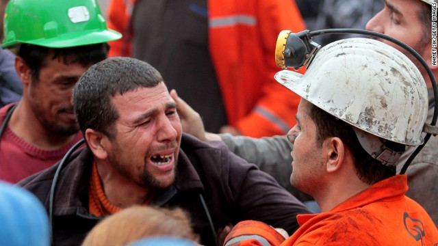 Miners react as bodies of their dead co-workers are carried out of the mine on May 14, 2014 in Soma, Turkey.