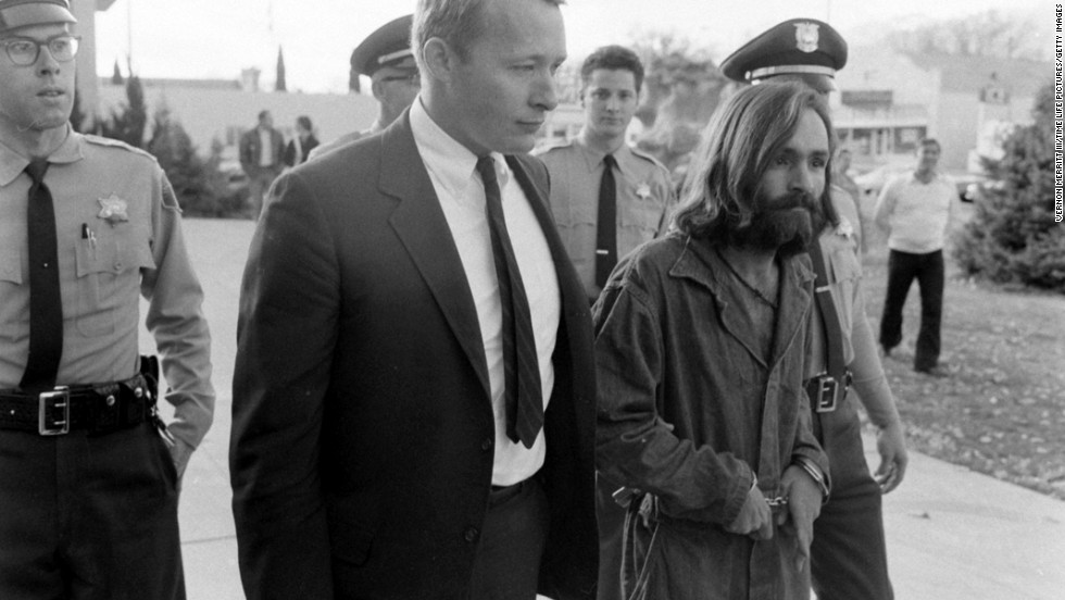 Cult leader Charles Manson is taken into court to face murder charges on December 5, 1969, in Los Angeles. At Manson's command, a small group of his most ardent followers brutally murdered five people at the Los Angeles home of film director Roman Polanski on August 8-9, 1969, including Polanski's pregnant wife, actress Sharon Tate. Manson was convicted for orchestrating the murders and sentenced to death. The sentence was later commuted to life in prison.
