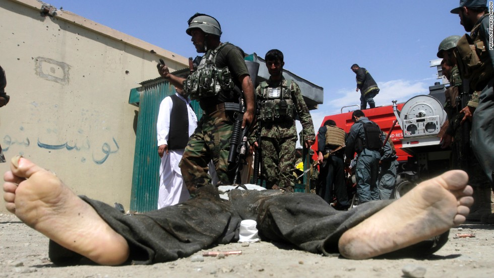 "Afghan security forces gather around the body of a Taliban insurgent after Taliban fighters stormed a government building Monday, May 12, in Afghanistan's Jalalabad province. Taliban militants <a href=""http://www.cnn.com/2014/05/12/world/asia/afghanistan-violence/index.html"">launched a wave of attacks</a> across the country, the first day of their annual spring offensive."
