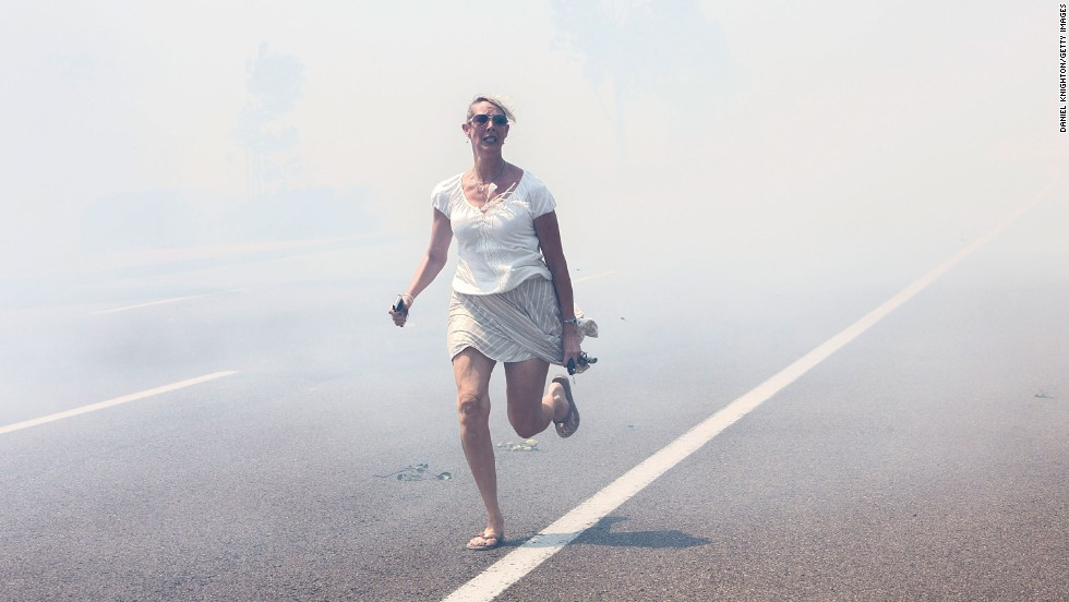 A woman flees a wildfire as it crosses a highway in Carlsbad on May 14.