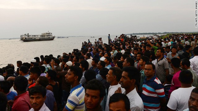 Bangladeshi residents gather near the site where a ferry capsized on the river Meghna in Munshiganj district, on May 15, 2014.