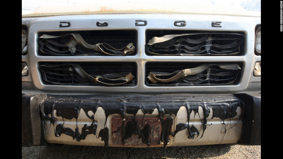 The grille of a pickup truck is left melted by a wildfire in San Marcos.