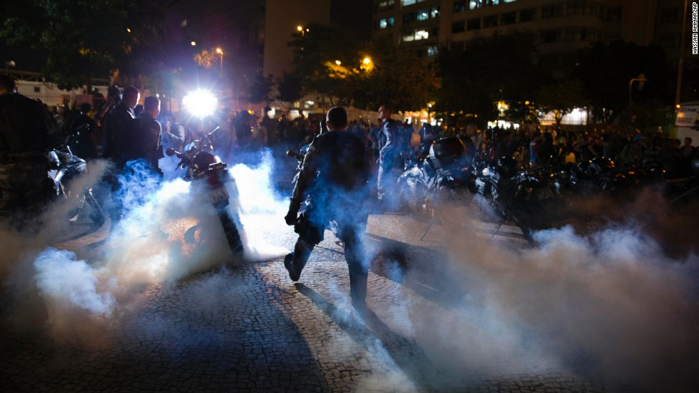 Police officers walk through a cloud of tear gas during a protest in Rio de Janeiro on May 15.