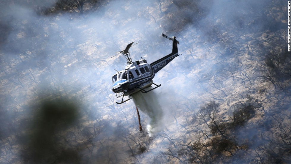 A helicopter from the San Diego County Sheriff's Department drops water on flames in the hills of San Marcos, California, on May 15.