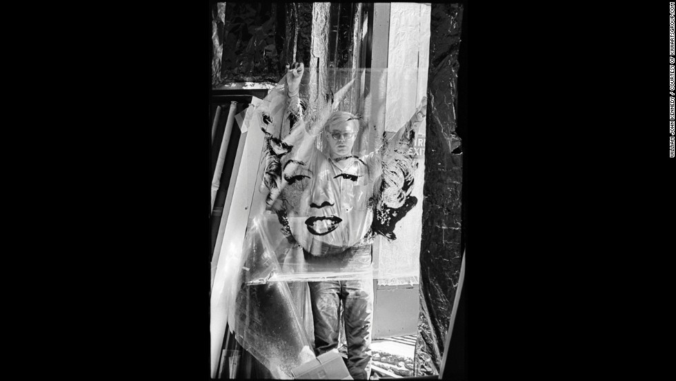 Artist Andy Warhol stands in the doorway of his studio, the Factory, in 1964, holding the acetate he used to make his famous Marilyn Monroe paintings. Warhol's work centered on famous personalities and iconic American objects, making him a leading figure in the pop art movement.