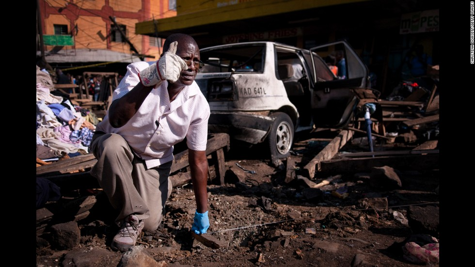 A member of a bomb squad measures the distance between the two blast sites in Nairobi on May 16. The explosions came the day after the United States, Australia and the United Kingdom issued travel alerts for Kenya.