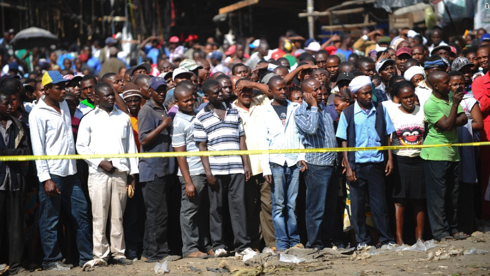 Onlookers gather behind police tape at the blast site in the Gikomba market area of the Kenyan capital on May 16.