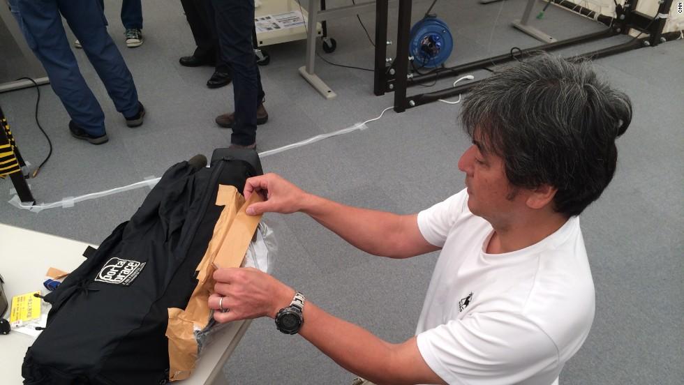 CNN cameraman Hidetaka Sato covers his gear to prevent radioactive contamination.