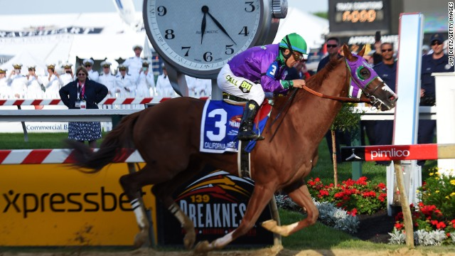 California Chrome, ridden by Victor Espinoza, crosses the finish line to win the  Preakness Stakes at Pimlico Race Course Saturday.