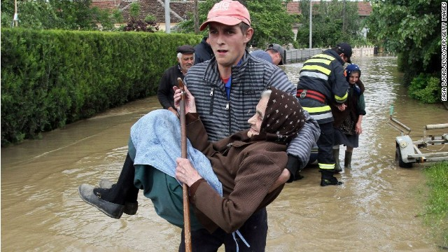 A Serbian rescuer carries an elderly woman out of her flooded house on May 17 in the village of Obrez, Serbia, south of Belgrade, on May 17.