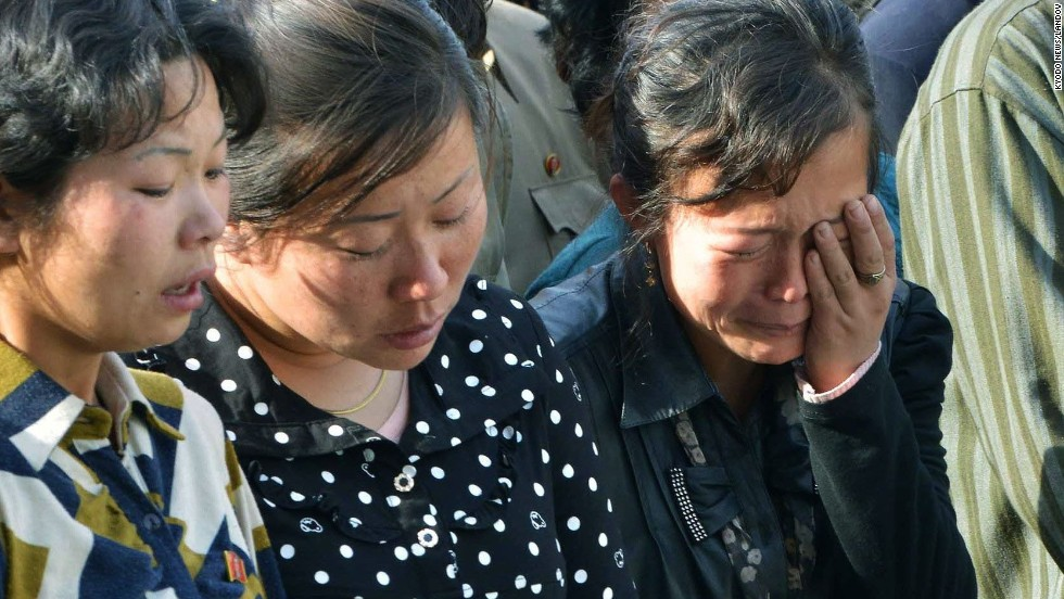 North Korean women listen as the official apologizes.