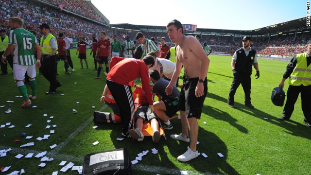 Fans of Osasuna get treatment after their match against Real Betis is halted after a metal fence gave way.