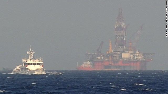 This picture taken on May 14, 2014 from a Vietnamese coast guard ship shows a Chinese coast guard vessel, left, sailing near China's oil drilling rig in disputed waters in the South China Sea.