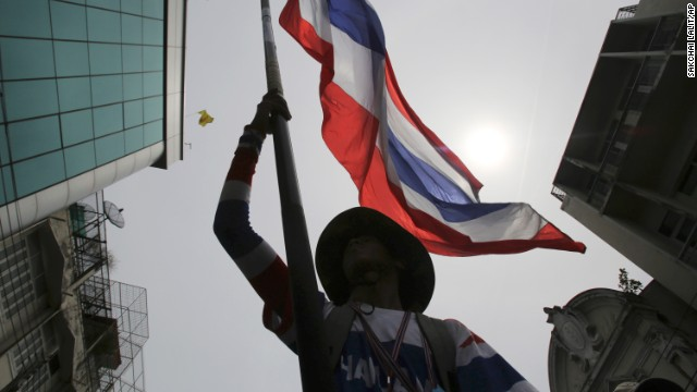 An anti-government protester waves a Thai national flag during a march through streets in Bangkok, Thailand, Monday, May 19, 2014. Thailand's political crisis deepened last week when the Constitutional Court removed Prime Minister Yingluck Shinawatra for nepotism along with nine Cabinet members in a case that many viewed as politically motivated. Protesters said Thursday, Yingluck's removal is not enough, though. She was simply replaced by Niwattumrong, who was a deputy premier from the ruling party.(AP Photo/Sakchai Lalit)