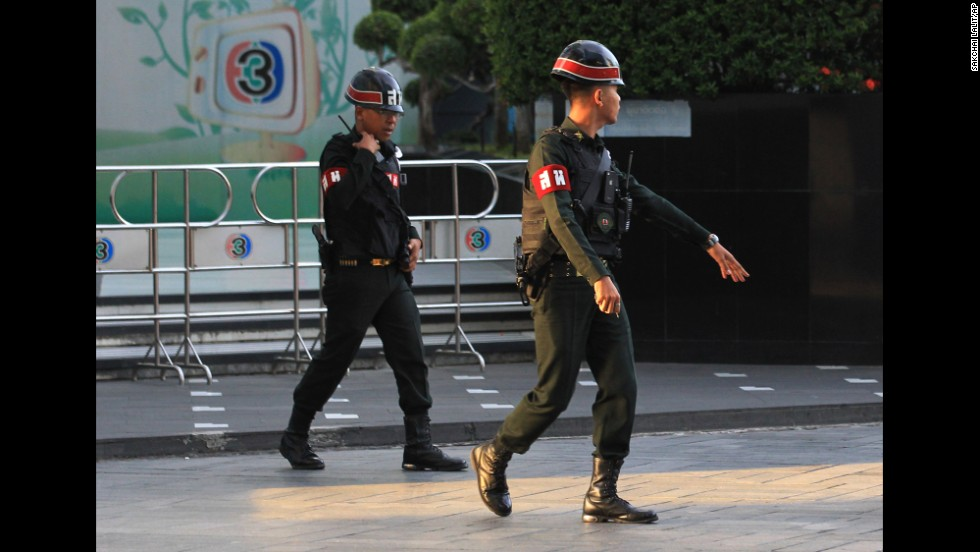 "Military police officers walk in front of the Thai TV 3 offices in Bangkok on May 20. In a statement read on Thai television, the military declared that all of the country's radio and television stations must suspend their normal programs ""when it is needed."""