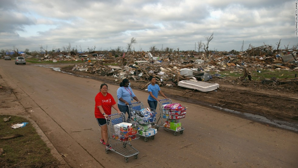 <strong>Then:</strong> From left, Jaqi Castro, Angelica Morris-Smith and Cetoria Petties walk through a tornado-ravaged neighborhood handing out supplies to residents and fellow volunteers on May 27, 2013.