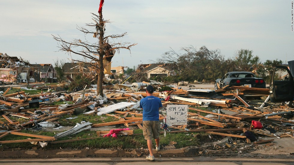 <strong>Then:</strong> Matt Bedoe stands in front of the home of his friend and co-worker Rick Jones on May 25, 2013. Jones, a 54-year-old postal worker, died when his house collapsed during the tornado.