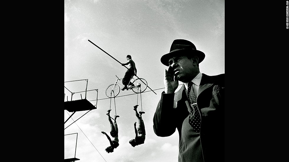 "<em>How the Circus gets set -- Balancing act with trapeze artists, 1948</em><br /><br />In 1948 Kubrick spent several days photographing the personalities in and around  America's largest circus. The images convey the cinematic language that would later define his films.<br /><br />Ortner-Kreil says the photos also demonstrate his knowledge of avant-gard and Bauhaus photography, which he would have encountered on his many trips to New York's Museum of Modern Art as a child.<br /> <br />""If you look at the point where this bar is cutting the rope it's really in the middle,"" she says. ""It appears to be a collage, not a photograph. All the different details are arranged very carefully, and he chooses the perspective of the director of the circus who is shouting at the artists and acrobats. He takes the camera down to underline the authority of the director."""