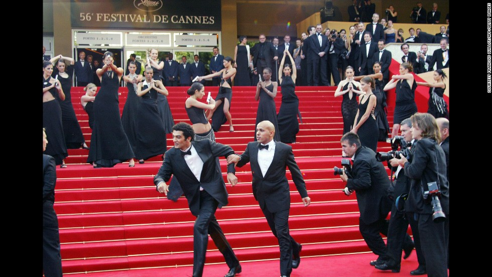 "Being chased by paparazzi and shot at by Bond girls is just another day in the life of french humorist duo Erik et Ramzy. The pair joke with the Bond girls upon arrival at the Palais des festivals before the screening of the film ""La Petite Lili"" by French director Claude Miller during the Cannes film festival in 2003."