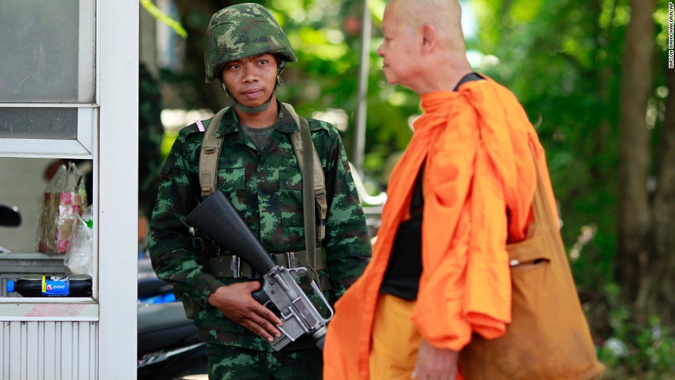 A Buddhist monk walks past a Thai soldier near a pro-government demonstration on the outskirts of Bangkok on Wednesday, May 21.