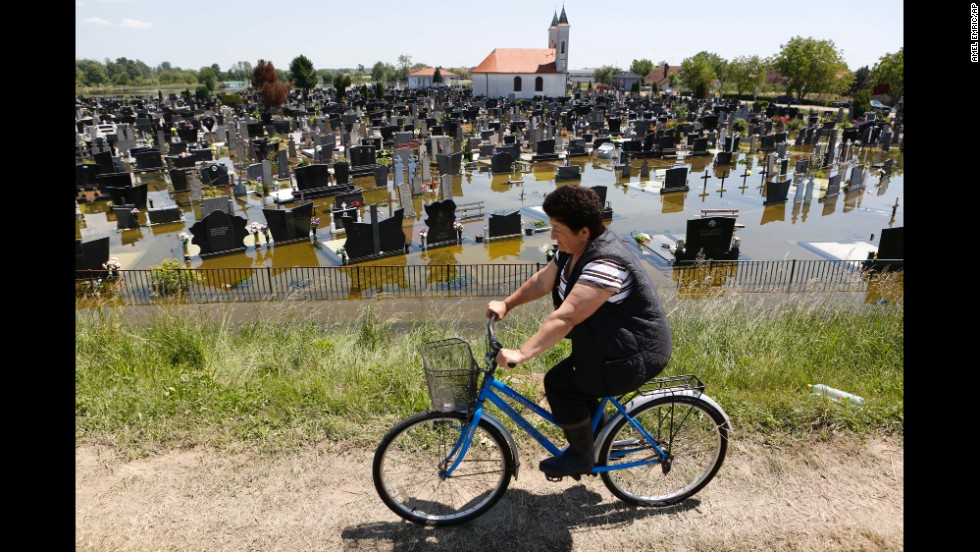 A woman rides a bicycle past a flooded cemetery in Domaljevac, Bosnia-Herzegovina, on Wednesday, May 21.
