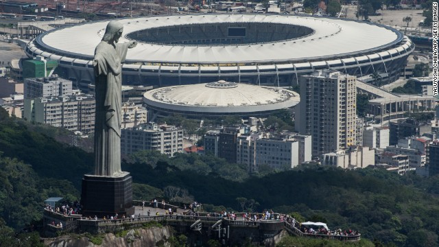 Aerial view of the Christ the Redeemer statue atop Corcovado Hill and the Mario Filho (Maracana) stadium in Rio de Janeiro, Brazil, on December 3, 2013. The Maracana stadium will host the Brazil 2014 FIFA World Cup and the 2016 Summer Olympics. AFP PHOTO / YASUYOSHI CHIBA JAPAN OUT (Photo credit should read YASUYOSHI CHIBA/AFP/Getty Images)