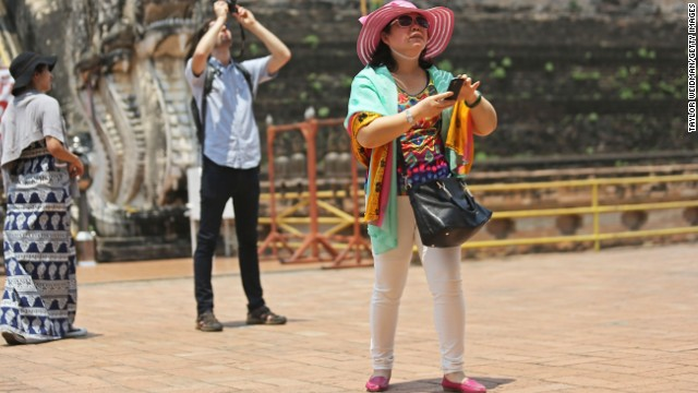 A Chinese tourist takes a photo in Thailand using a smartphone.
