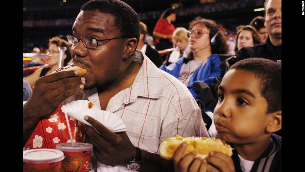 Baseball fans eat hot dogs during a game at New York's Shea Stadium in 2003.