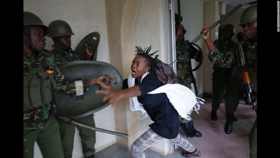 A woman flees as a riot police officer beats her with a baton Tuesday, May 20, in Nairobi, Kenya. Hundreds of Nairobi University students took to the streets and faced riot police as they protested against a proposed increase in school fees.