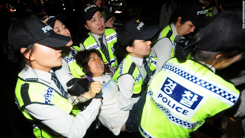"Police in Seoul, South Korea, detain a protester during a march Saturday, May 17, for victims of <a href=""http://www.cnn.com/2014/04/15/asia/gallery/south-korea-sinking-ship/index.html"">the sunken ferry Sewol</a>. The Sewol sank en route to the resort island of Jeju on April 16, leaving more than 304 people dead or missing."