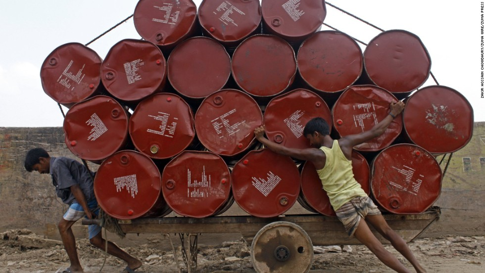 Two laborers haul barrels on a wooden cart Tuesday, May 20, in Dhaka, Bangladesh.