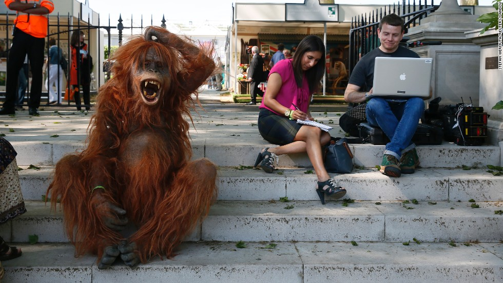 A man dressed as an orangutan sits next to members of the press during media day at the Chelsea Flower Show in London on Monday, May 19.