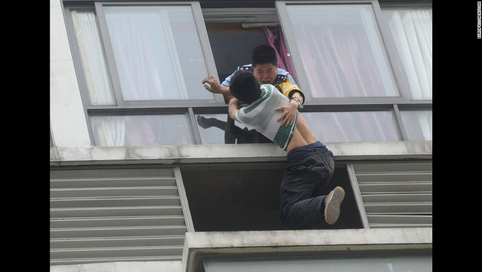 A suicidal man, bottom, fights off a police officer trying to prevent him from jumping off the sixth floor of a building in Chengdu, China, on Wednesday, May 21. The man eventually was talked down by a woman he had recently broken up with, a police spokesman said.