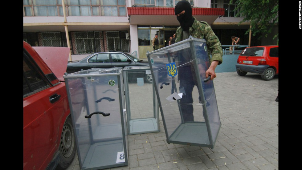 A pro-Russian activist carries a ballot box away from a polling station in Donetsk, Ukraine, as he prepares to smash it on May 23.