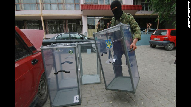 A pro-Russian activist carries a ballot box away from a polling stationin Donetsk, Ukraine, as he prepares to smash it on May 23.