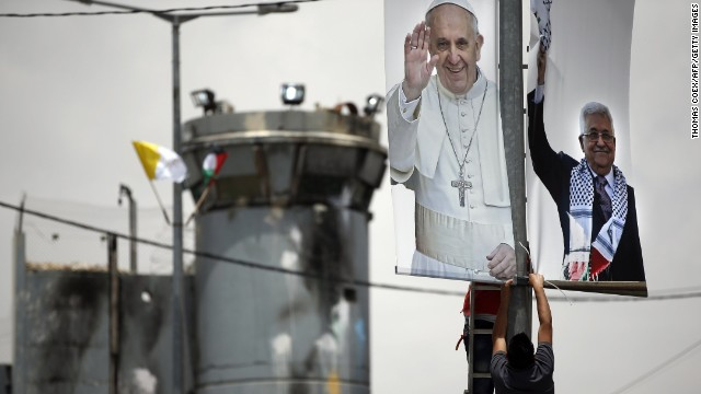 :Palestinian workers put up a poster bearing portraits of Pope Francis (L) and Palestinian president Mahmud Abbas near a look out point from the Israeli separation barrier dividing the West Bank and Jerusalem on May 21, 2014. Pope Francis said his upcoming trip to the Middle East would be 'purely religious' and aimed mainly at improving relations with other branches of Christianity and praying for peace in the region. AFP PHOTO / THOMAS COEX (Photo credit should read THOMAS COEX/AFP/Getty Images)